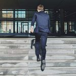 business person running up concrete steps to office building